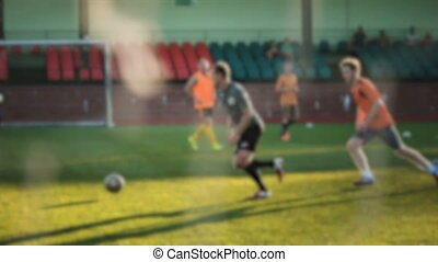 Footballer runs and passes the ball, amateur soccer game at...