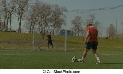 Footballer scoring a goal after penalty kick - Young...