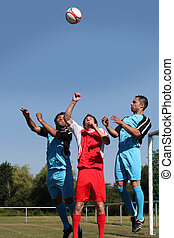 Footballers jumping for ball