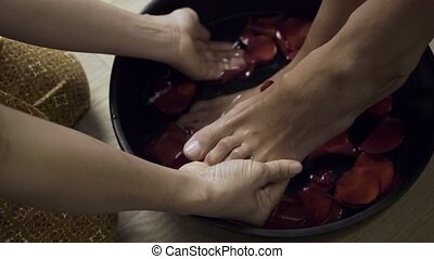 Woman washing beautiful legs in bowl. - Footbath in spa...