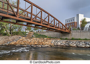 bike trail and footbridge - Cache la Poudre River at whitewater park in downtown of Fort Collins Colorado with Powerhouse Energy Campus of Colorado State University in background
