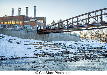 footbridge over Cache la Poudre River at newly developed whitewater park in downtown of Fort Collins Colorado with Powerhouse Energy Campus of Colorado State University in background, winter sunset scenery