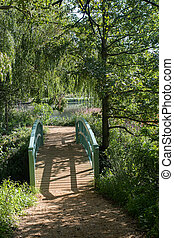 Footbridge to English countryside lake in Summer gardens