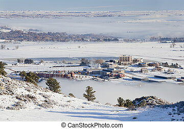 foothills of Fort Collins, Colorado with university building and solar farm, a winter scenery with snow and fields of fog