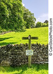Footpath sign on a sloping green field
