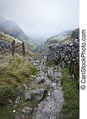 Footpath through mountains in Autumn foggy morning -...