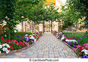 Footpath to the gate - Colorful brick footpath with flowers ...