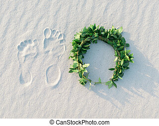 Footprint and green laurel wreath on white sand tropical beach.