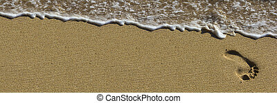 Footprint at beach with waves