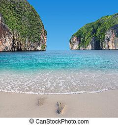 Footprint on the beach with nice sea and sky