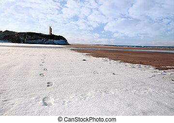 footprint tracks in snow on empty beach with castle