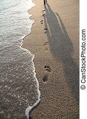 Footprints and shadow on the beach sand