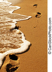 Footprints by the sea - Footprints in the sand beeing washed...