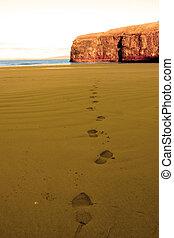footprints in sandy empty beach on a beautiful winters day