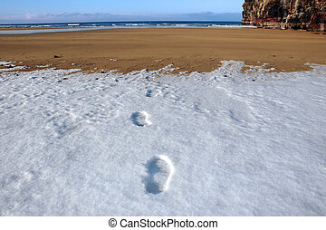 footprints in snow on empty beach on a cold winters day