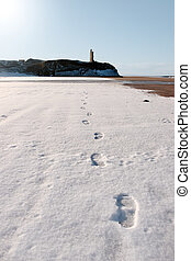 footprints in snow on empty beach with castle
