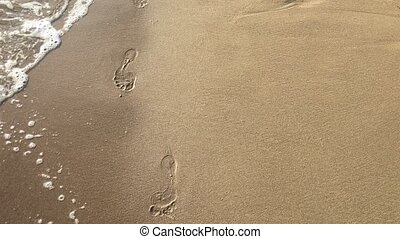 Footprints on the beach left behind for wave to wash off abstract past and memory