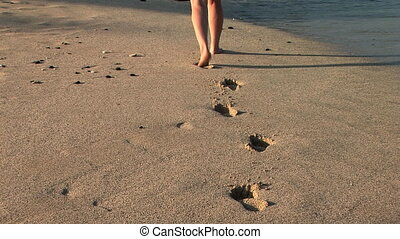 Footprints in the sand - Woman walking alone on the beach,...