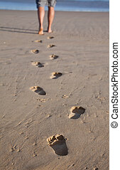 Footprints in wet sand in a line with a man walking to the sea