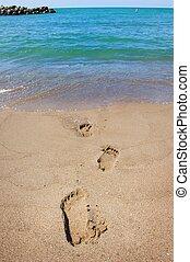 Footprints leading into a blue ocean