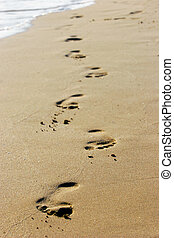 footprints on empty sand beach