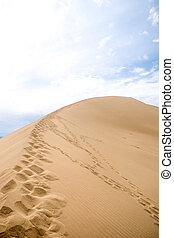 footprints on sand dune background of mountains