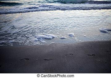 Footprints on sandy beach against foamy waves