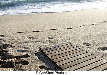 Footprints on the beach. Wavy sea.