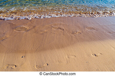 Footprints on the sandy beach being washed away