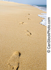 footprints on the shoreline - Close up view of a wave in the...