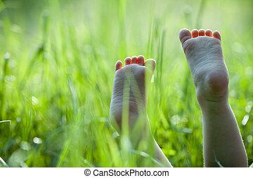 foots - Happy children lying on green grass