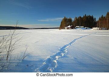 Footsteps on frozen solid lake Norsjon in Vasterbotten, Sweden