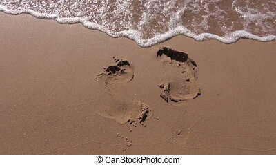 footsteps on wet resort beach sand and sea wave