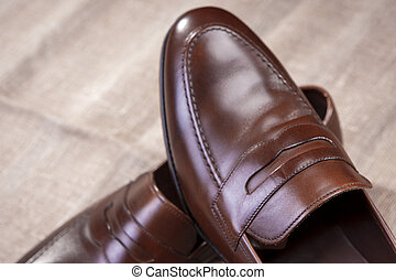 Footwear Concepts and Ideas. Closeup of Pair of Brown Stylish Leather Penny Loafer Shoes Placed On Mesh Surface.