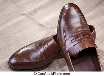 Footwear Concepts and Ideas. Pair of Brown Stylish Leather Penny Loafer Shoes Placed On Mesh Surface. Against Black