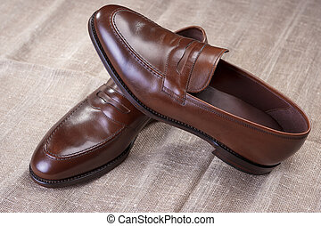 Footwear Concepts and Ideas. Pair of Brown Stylish Leather Penny Loafer Shoes Placed On Mesh Surface