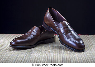 Footwear Concepts and Ideas. Pair of Stylish Expensive Modern Calf Leather Brown Penny Loafers Shoes.Closeup Shot.