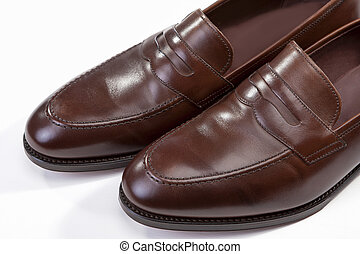 Footwear Concepts. Extreme Closeup of Leather Stylish Brown Penny Loafer Shoes Together Against White Background.