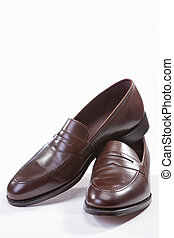 Footwear Concepts. Leather Stylish Brown Penny Loafer Shoes Together Against White Background.
