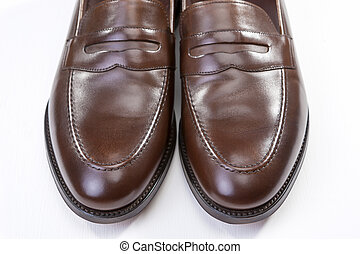 Footwear Concepts. Pair of Stylish Brown Penny Loafer Shoes Against White Background. Placed Together Closely.