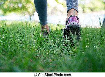 Footwear on female feet running on green grass - Closeup...