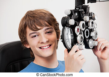 For Better Vision - Smiling boy holding phoropter while...