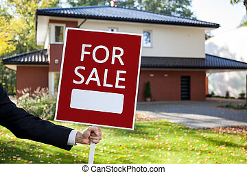 For sale sign - Close-up of real estate agent holding for...