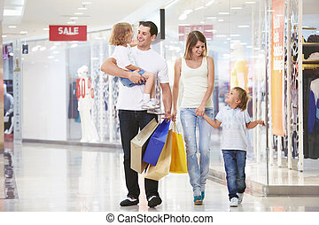 For shopping - A young family of four with children in the...