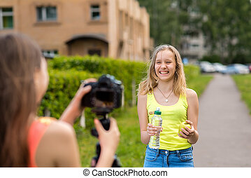For the girl student. Writes video to the camera. In the hands holding an apple in a bottle of water. Write down a vlog and a blog about proper nutrition. Happy smiling. Laughing in nature.