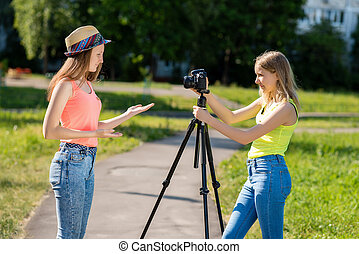 For the girl's girlfriend. Summer in nature. They are dressed in casual clothes. Conduct a conversation. Record vlog and blog subscribers. Record video lesson for Internet. Use camera with tripod.