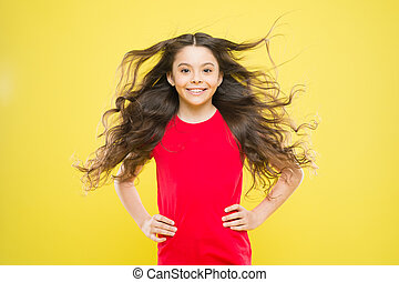 For the look of the future. Happy child on yellow background. Small child smiling with beauty look. Brunette female child with long wavy hair. Cute little child with adorable smile