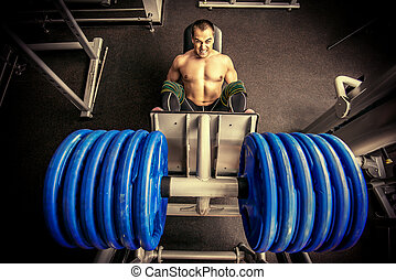 force - Muscular man weightlifter doing leg presses in gym....