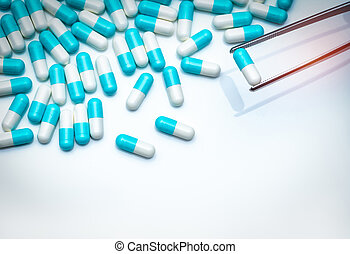Forceps pick white-blue capsule from group of capsule pills. Drugs choose. Antibiotic drug selection. Antibiotic drug resistance concept. QA and QC in pharmaceutical factory concept. Drugs of choice.