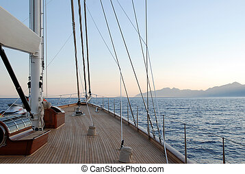 fore deck of a schonner type of yacht is seen in the photo. the boat was cruising from Marmaris to Bodrum at a speed of 10 knots. The photo was taken just after sunset in yacht charter (blue voyage) in Turkey